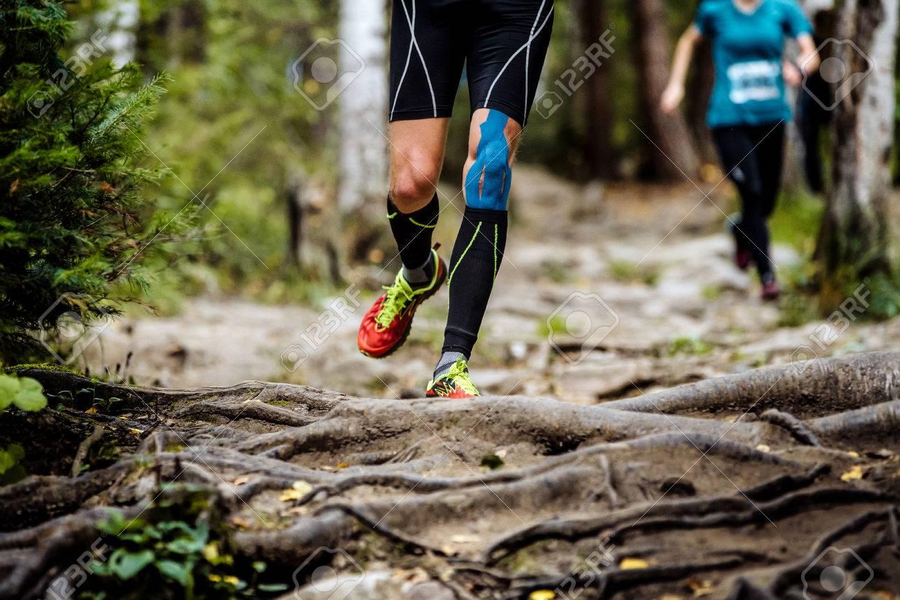running marathon runner in forest. legs in compression socks, knee taping - 62790920