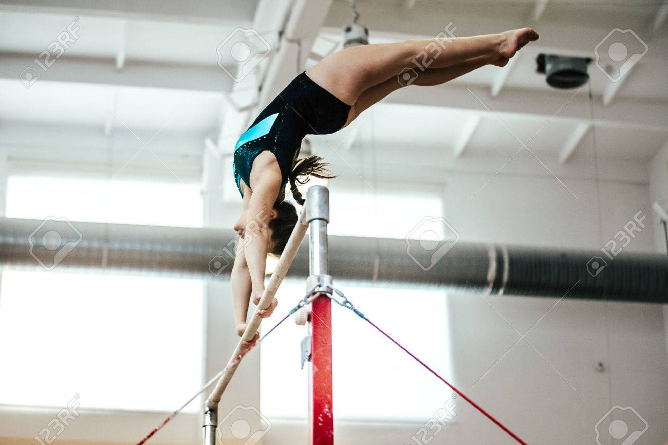 girl athlete gymnast exercises on uneven bars - 71879922
