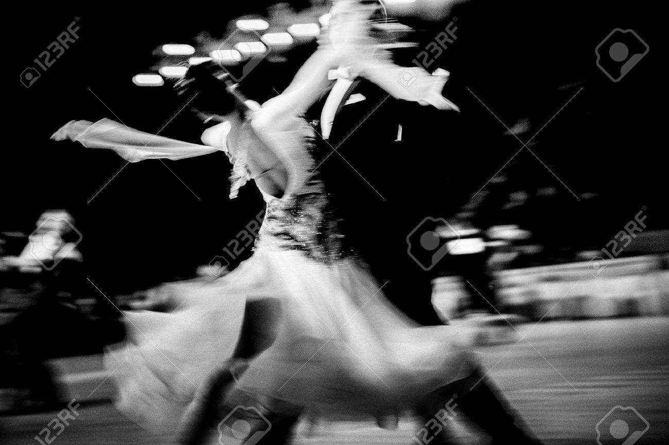Blurred couple dancers competition in ballroom dancing black