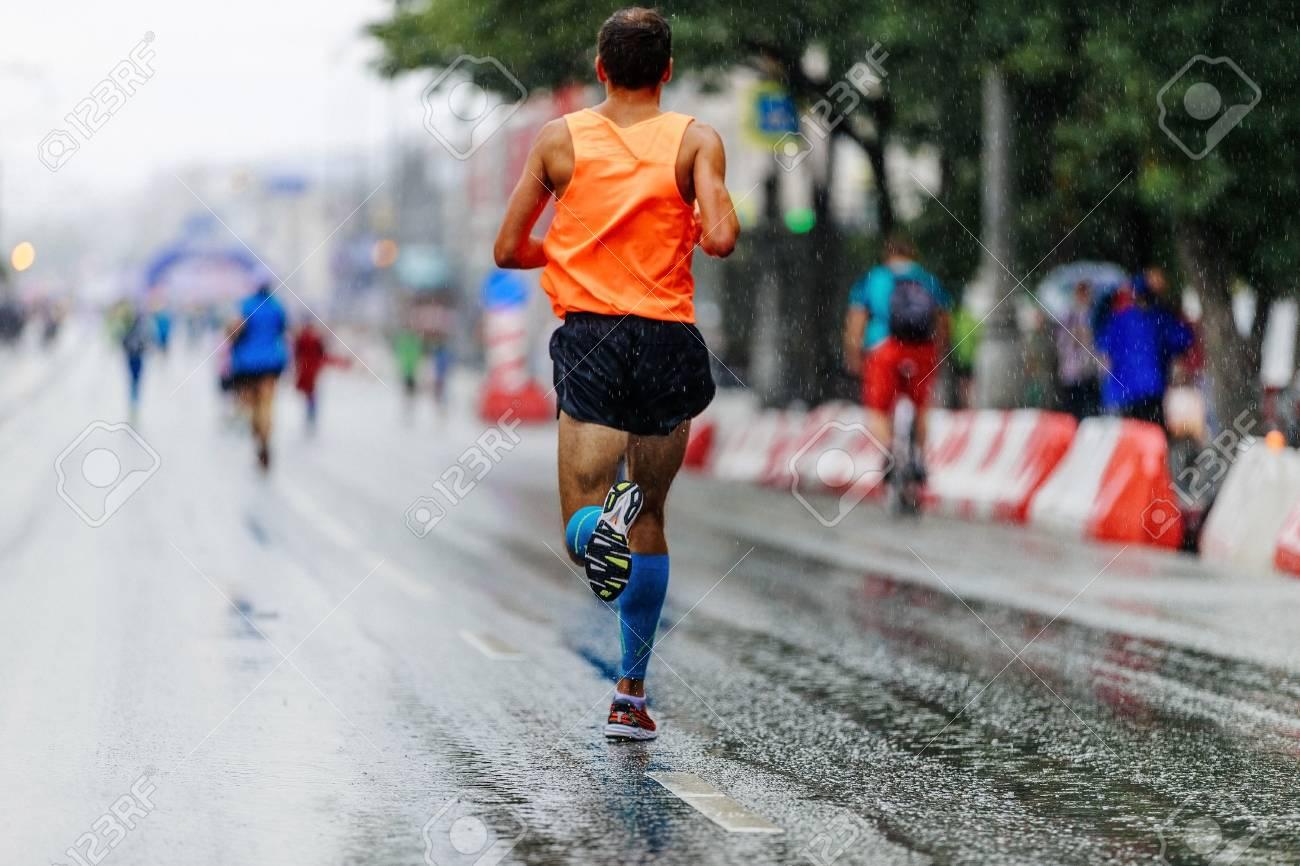 0ae159bb0a back man athlete runner running city marathon in rain Stock Photo - 84315984