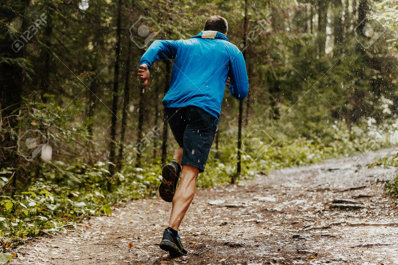 muscular male runner fast running forest trail in rain - 85478886