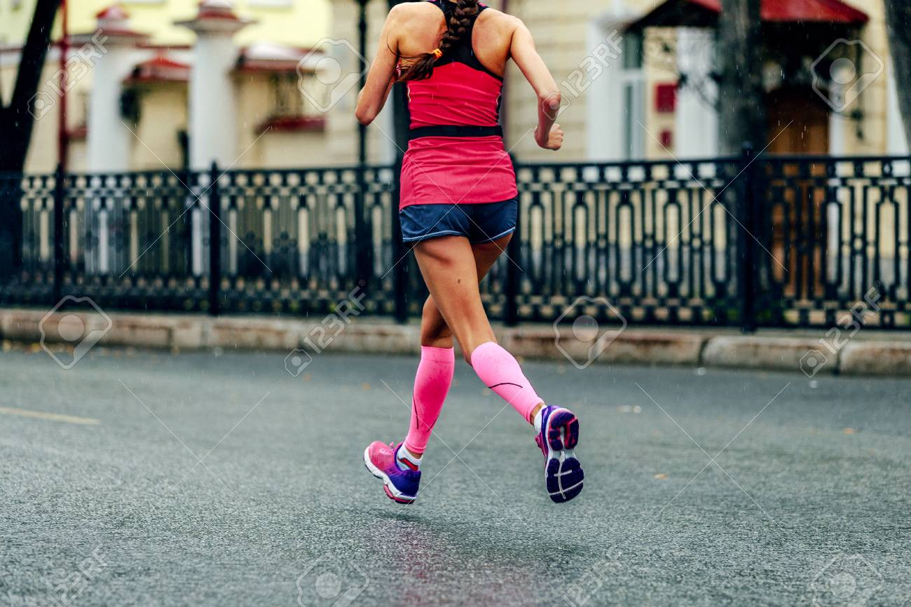 6d8ffa657cc female runner in pink compression calf sleeves running marathon under rain  drops Stock Photo - 97141173
