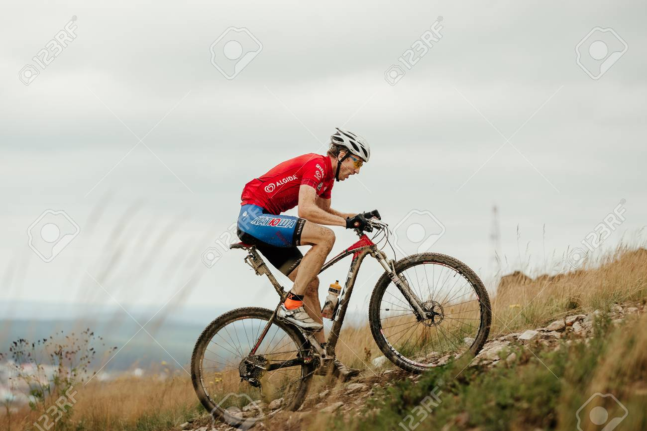 V.Ufaley, Russia - August 12, 2018: man cyclist mountain biker riding uphill during race XCM Big stone - 115037490