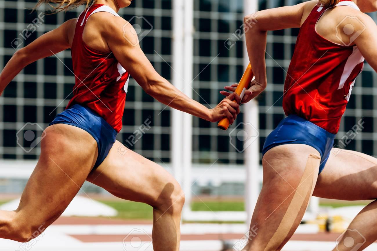 relay race passing of baton women team runners - 107725515