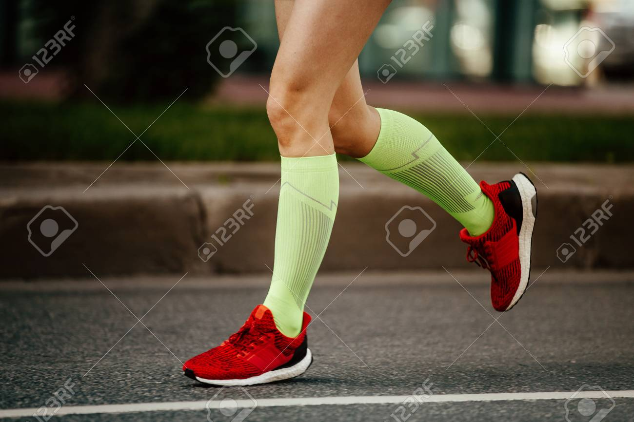 women feet runner in green compression socks and red running shoes - 107725399