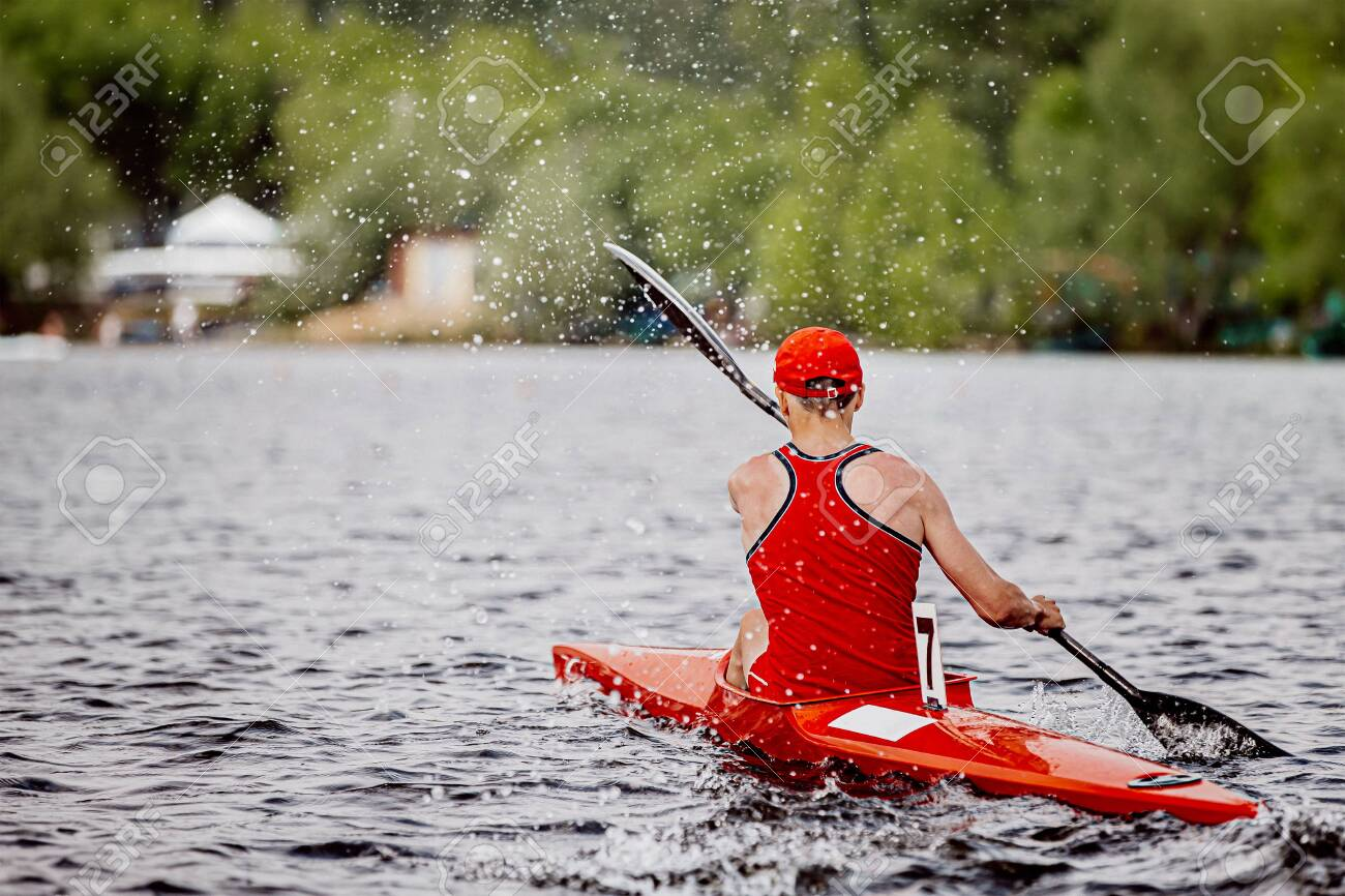 back athlete kayaker rowing kayaking competition. splashes and water drops - 138098590