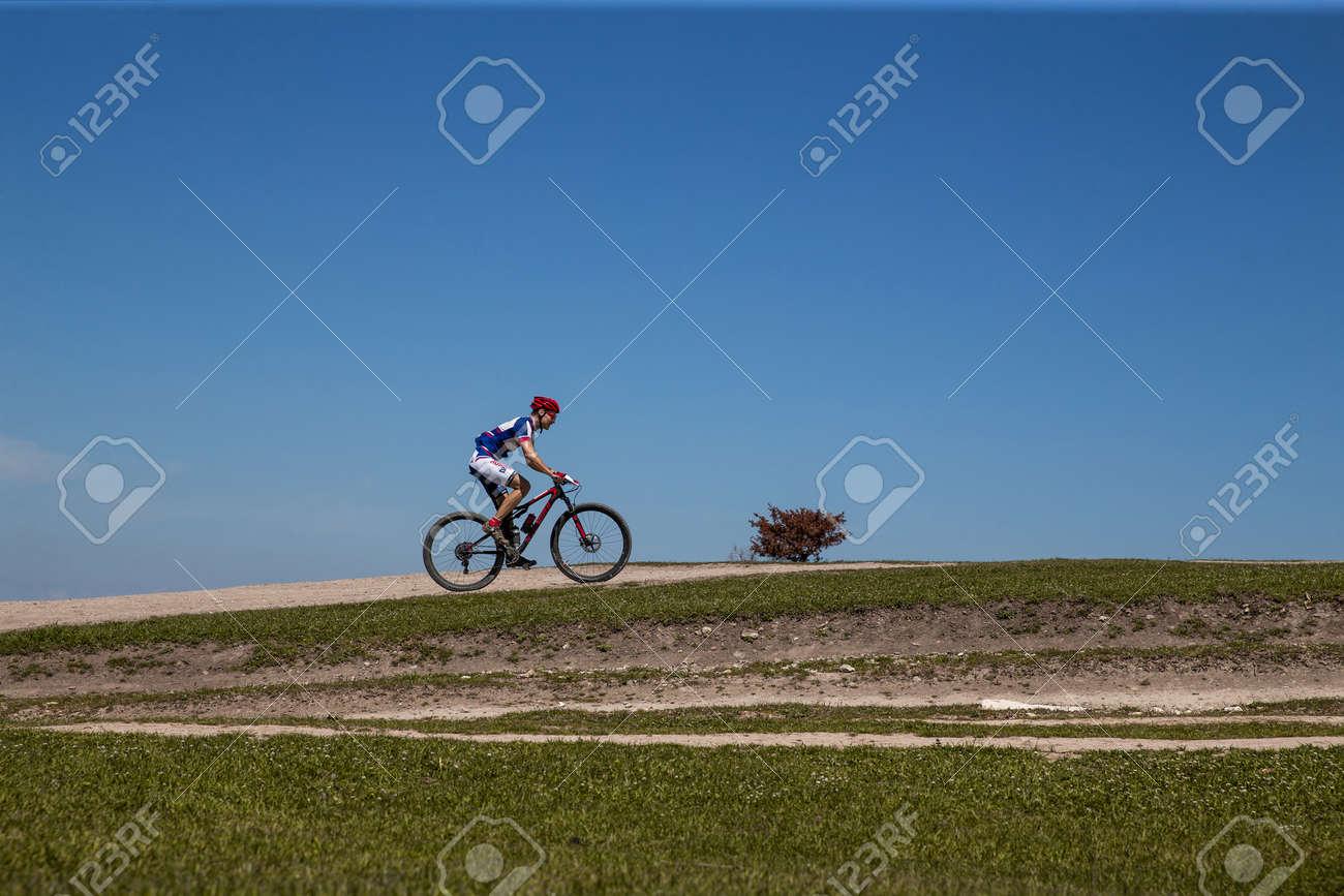 Yalta, Russia - April 30, 2021: man athlete mountain biker riding trail during MTB race - 170784668