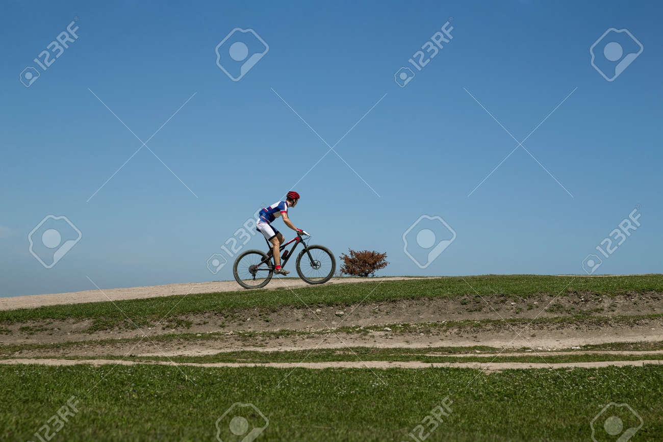 man on bicycle riding on green hill in background blue sky - 170066624