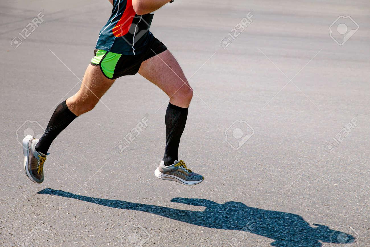 legs male runner in black compression socks run road - 170826243