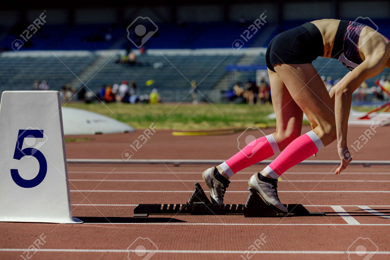 girl athlete in compression socks running from starting blocks - 172752649