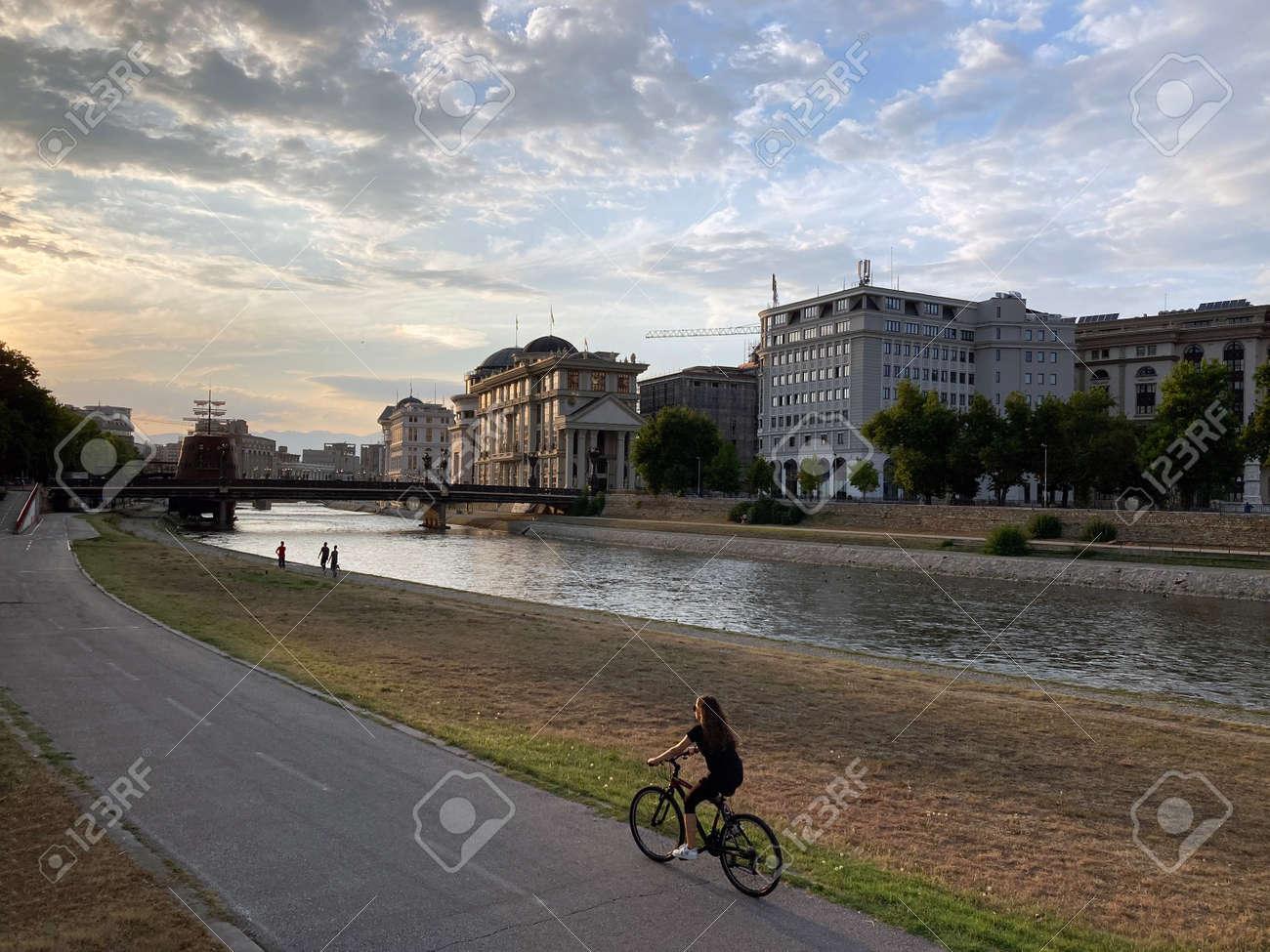 girl on bike riding in embankment during sunset - 173398995