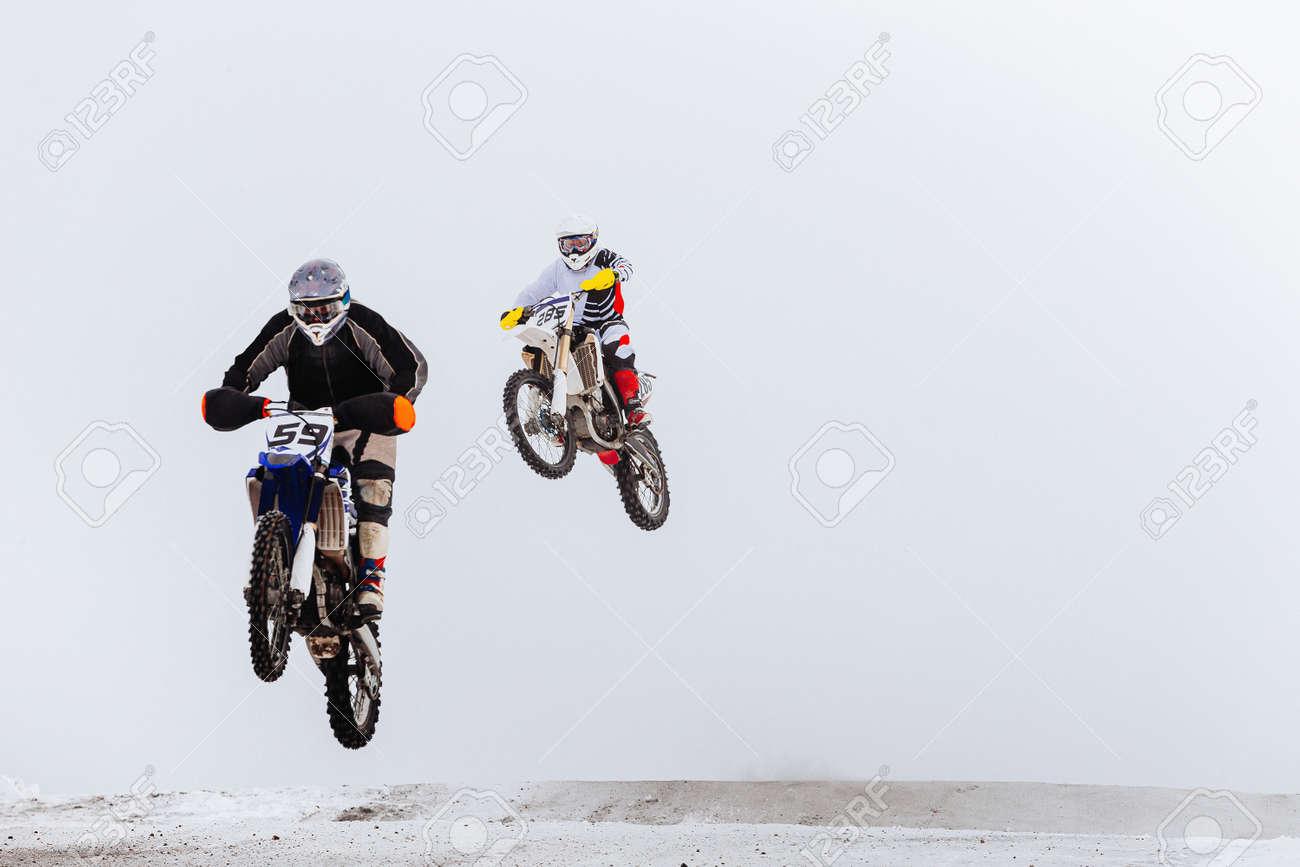 two motorcycle racers jump winter enduro race - 173829188