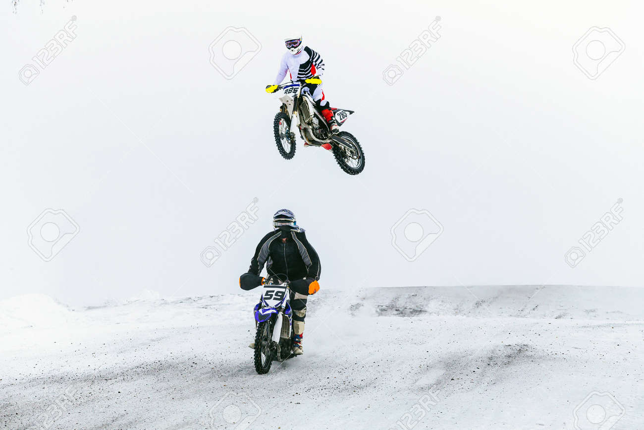 two motorcycle racers riding on snowy trail race - 173828713