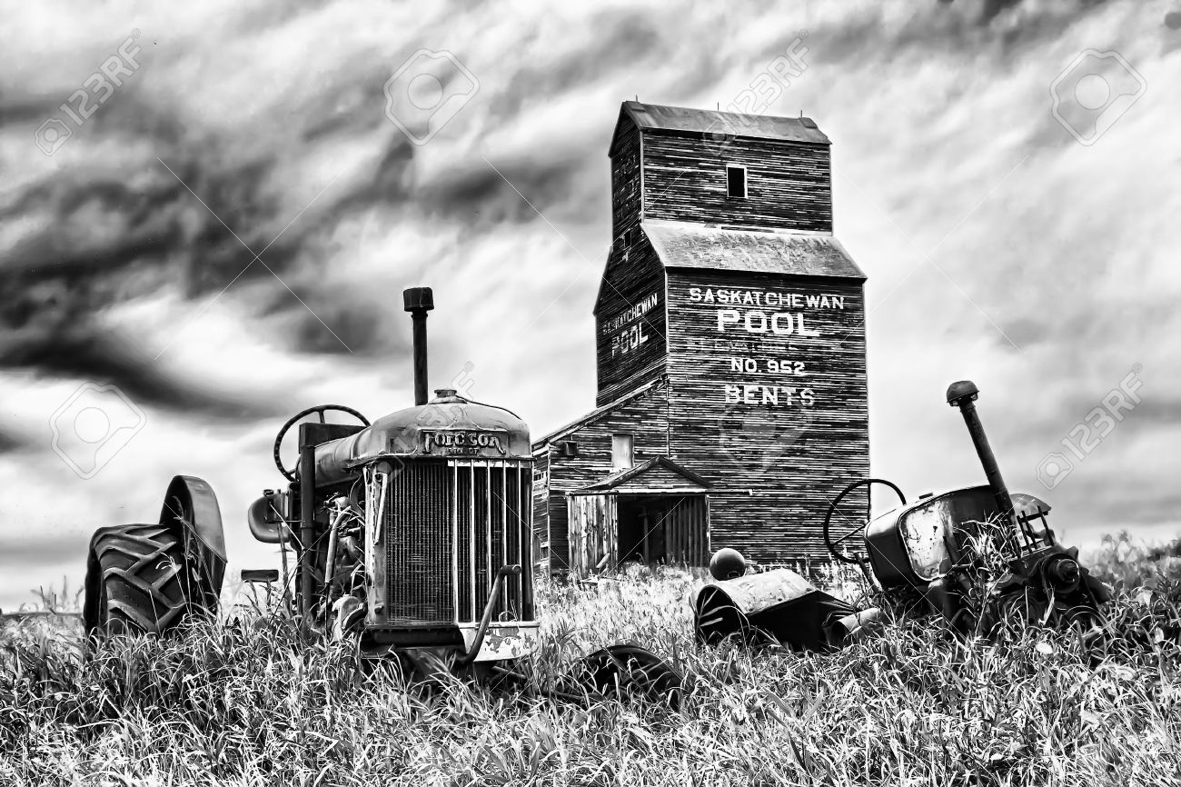Old abandoned tractor near a grain elevator in the ghost town of Bents in central Saskatchewan, Canada Stock Photo - 9454136