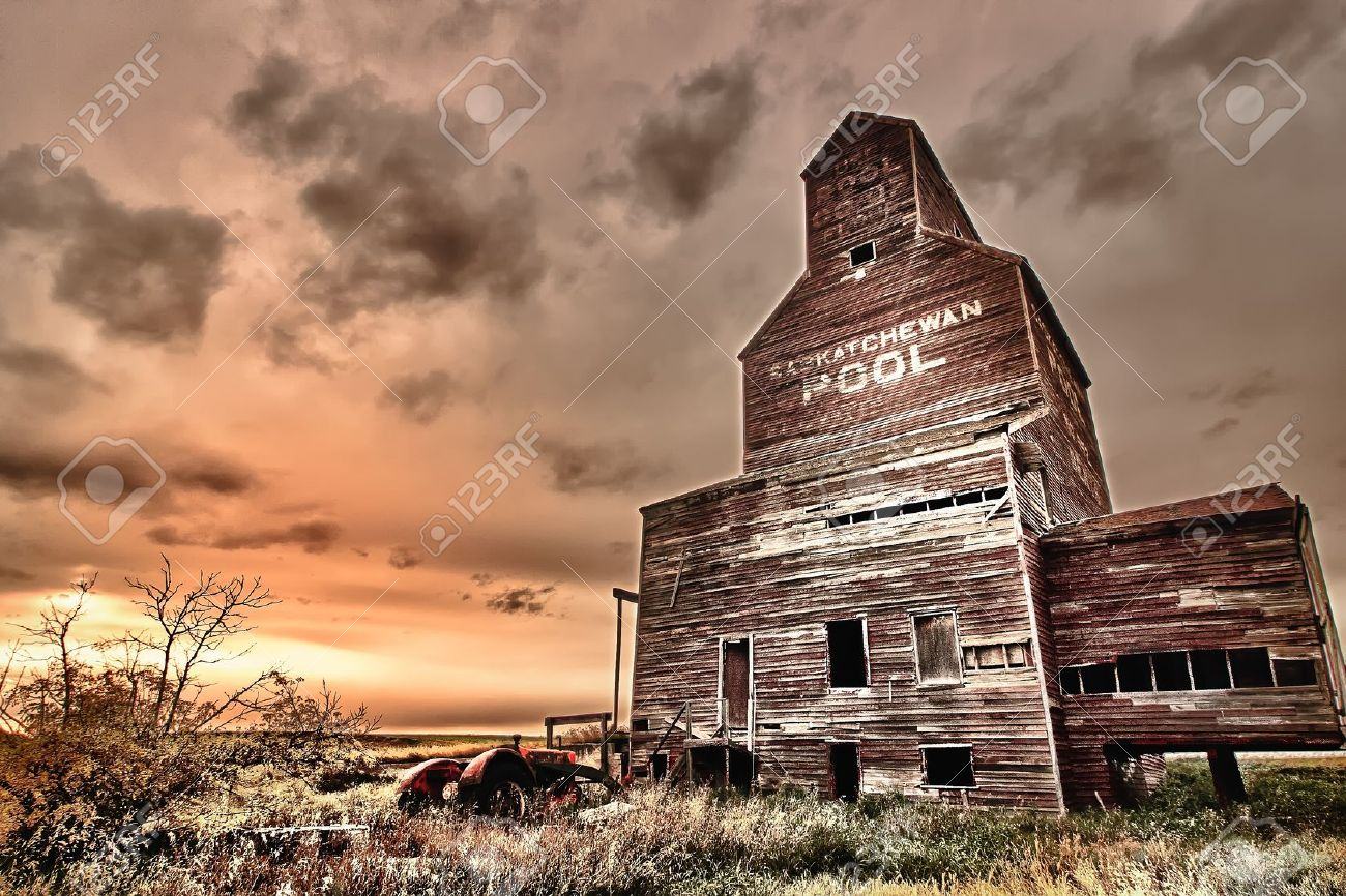 Old abandoned tractor near a grain elevator in the ghost town of Bents in central Saskatchewan, Canada Stock Photo - 9454175