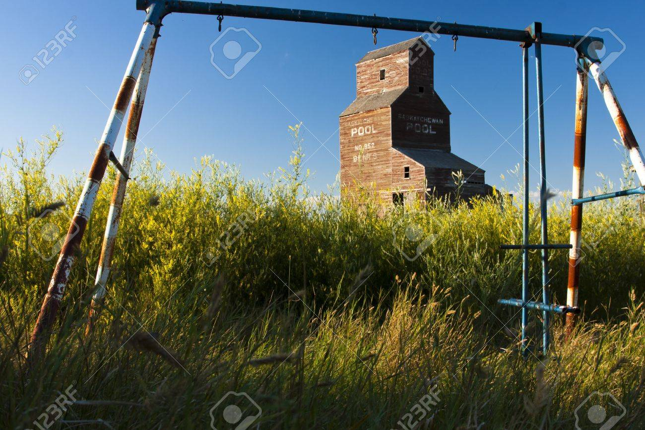 Old Swing Set Abandoned In The Tall Grass With An Old Grain Elevator