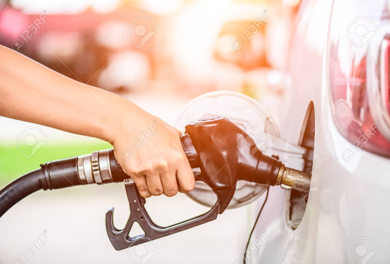 Closeup of woman hand holding a fuel pump at a station. - 91455583