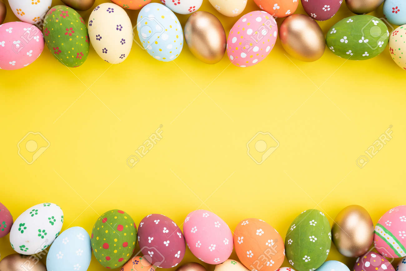 Happy easter! Close Up Colorful Easter eggs on yellow paper background. Happy family preparing for Easter. - 121242632