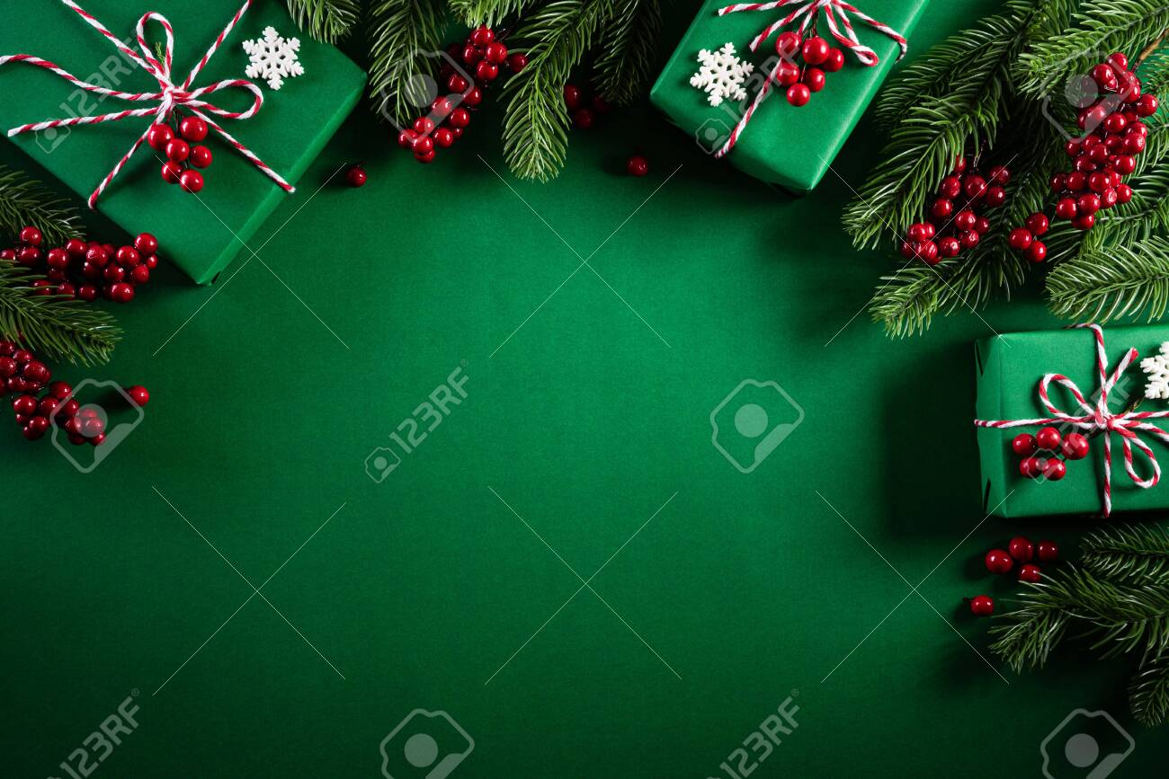 Christmas background concept. Top view of Christmas green gift box with decoration, spruce branches and red berries on green background. - 134017588