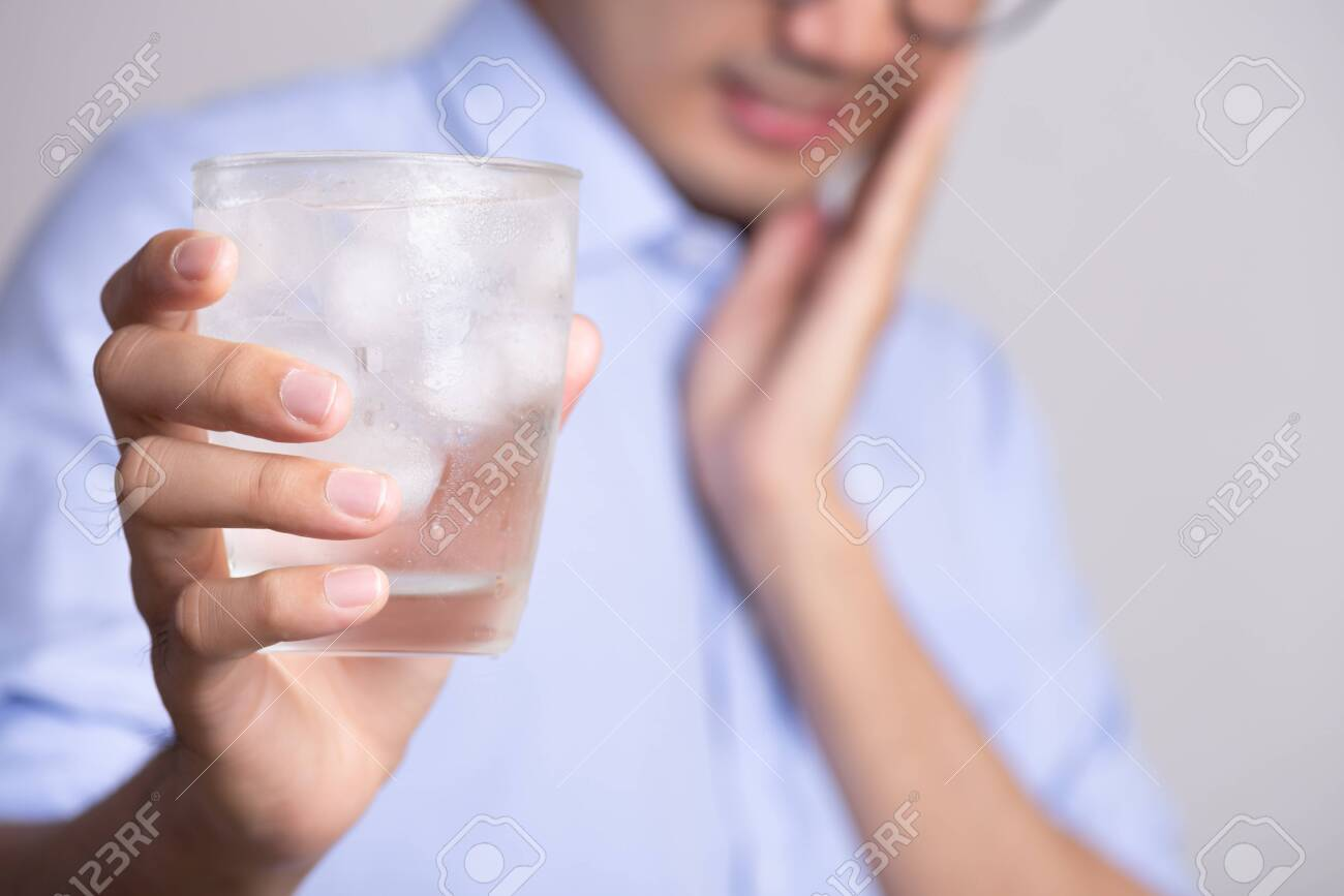 Young man with sensitive teeth and hand holding glass of cold water with ice. Healthcare concept. - 141662740