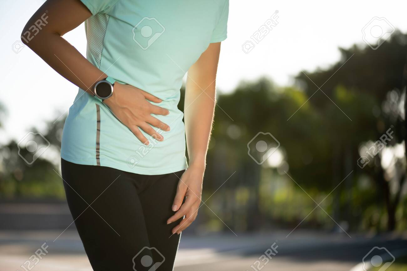Sport girl have stomach pain after jogging work out in park. Healthcare and Sport concept. - 141662756