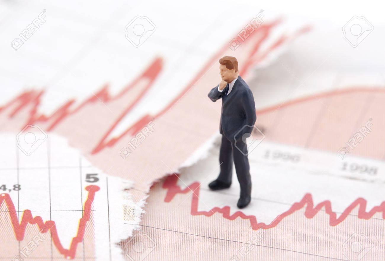Financial crisis. Figure of businessman on financial charts Stock Photo - 12105807