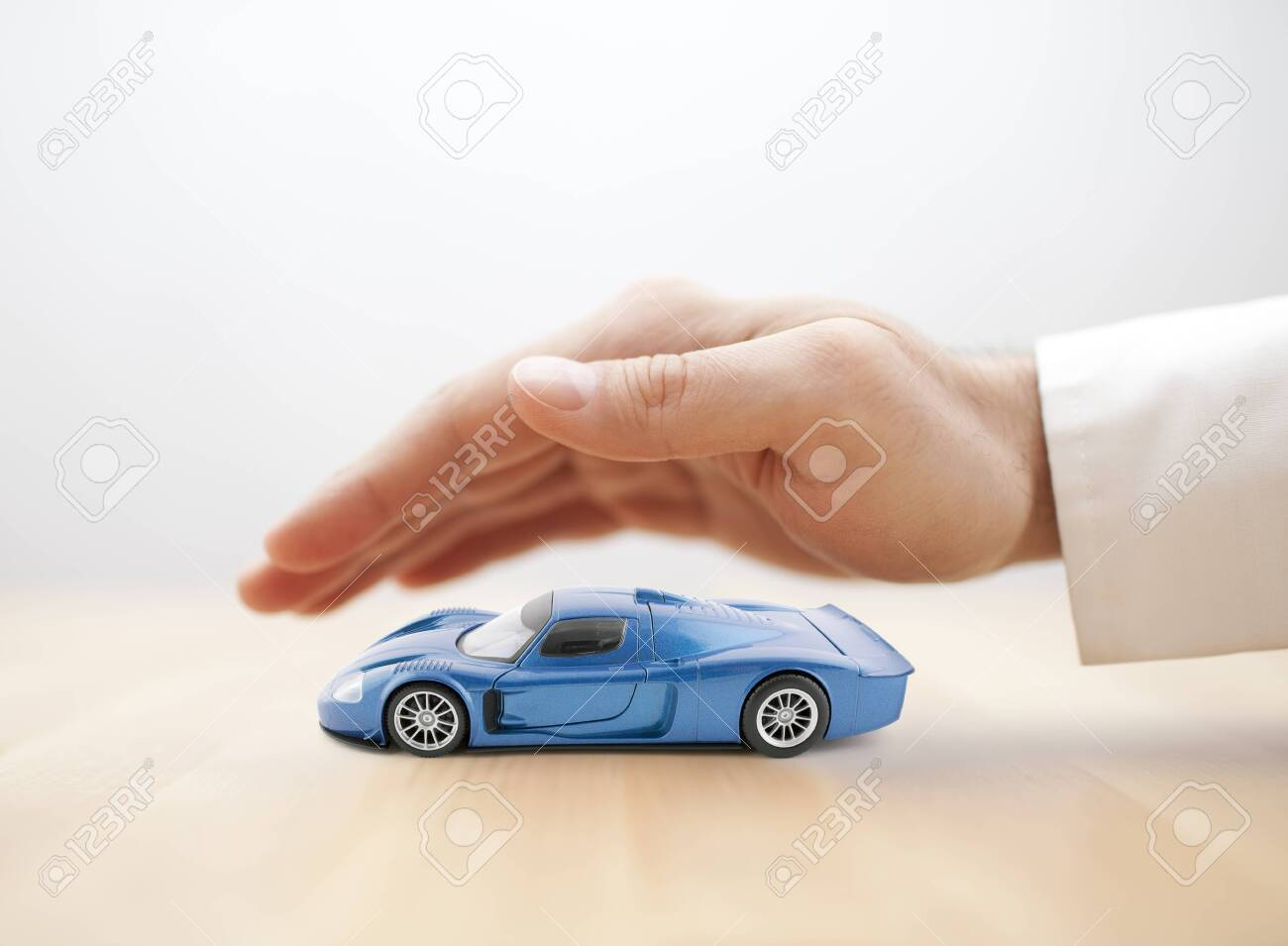 Car insurance concept with blue car toy covered by hand - 123611461