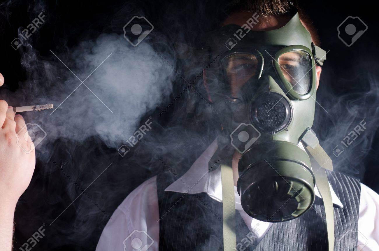 Man wearing a gas mask for protection against cigarette smoke Stock Photo - 11536767