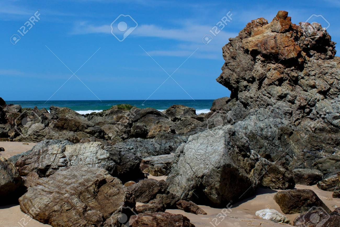 Beach rock formation with ocean, blue sky in background Stock Photo - 16403421