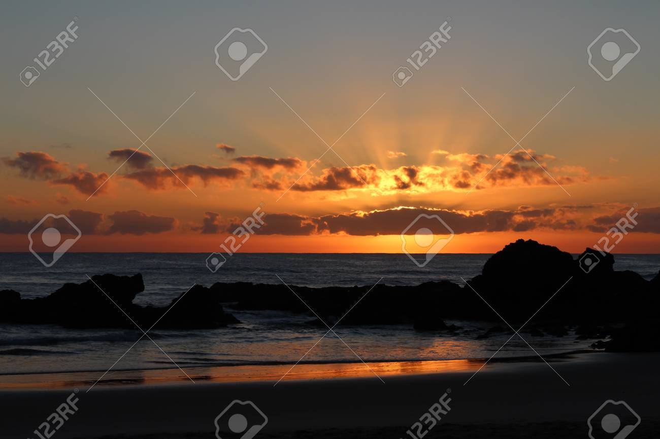 Beach sunrise with rocks in silhouette Stock Photo - 16403390