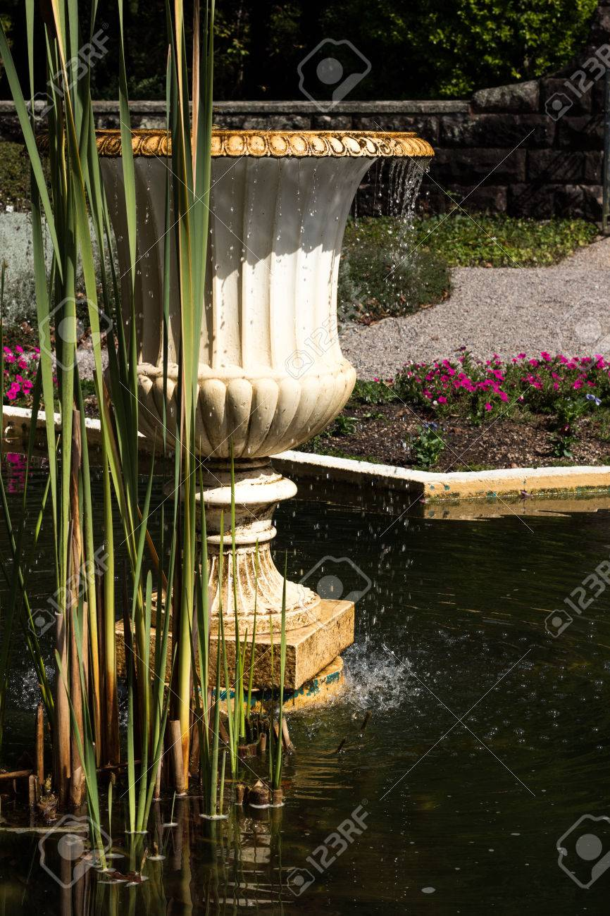 Garden Water Fountain In Pond With Reeds And Plants In Background ...