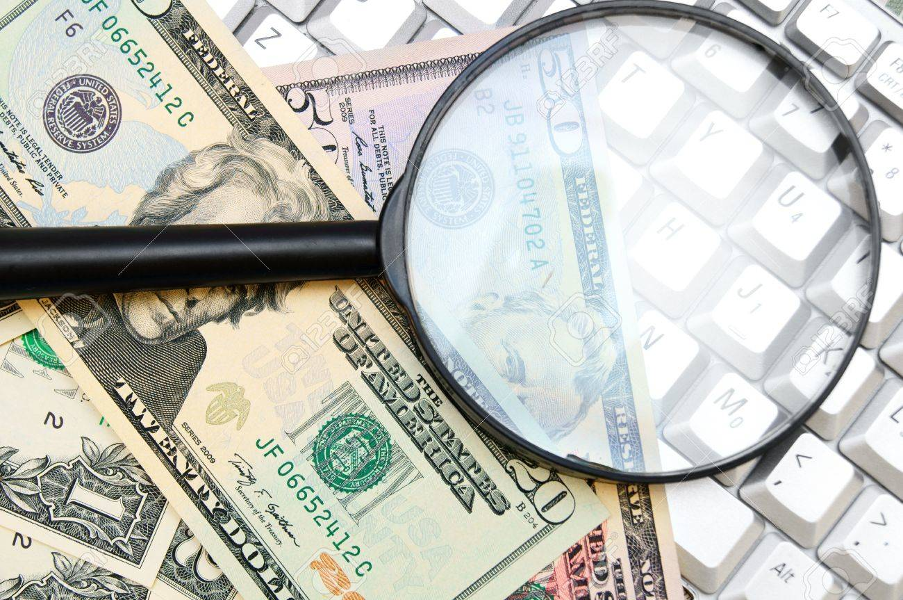Money and magnifier for the keyboard. Stock Photo - 17237113