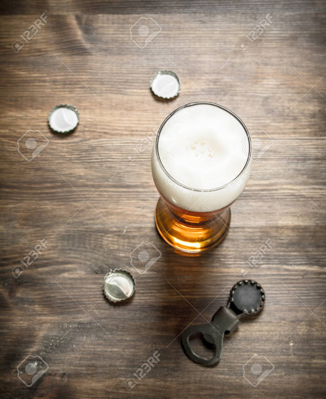 Glass Of Beer With Stoppers And A Bottle Opener On A Wooden