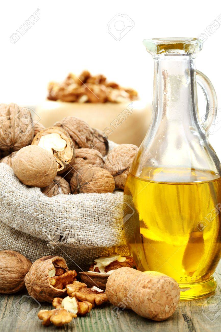 Walnut oil  and nuts in a bag on a wooden table Stock Photo - 15140501