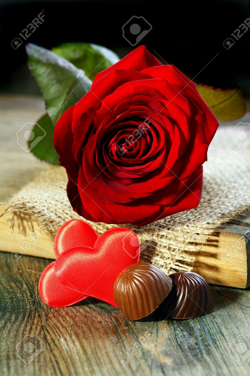 Two red hearts, chocolates and roses on a wooden table Stock Photo - 16942864