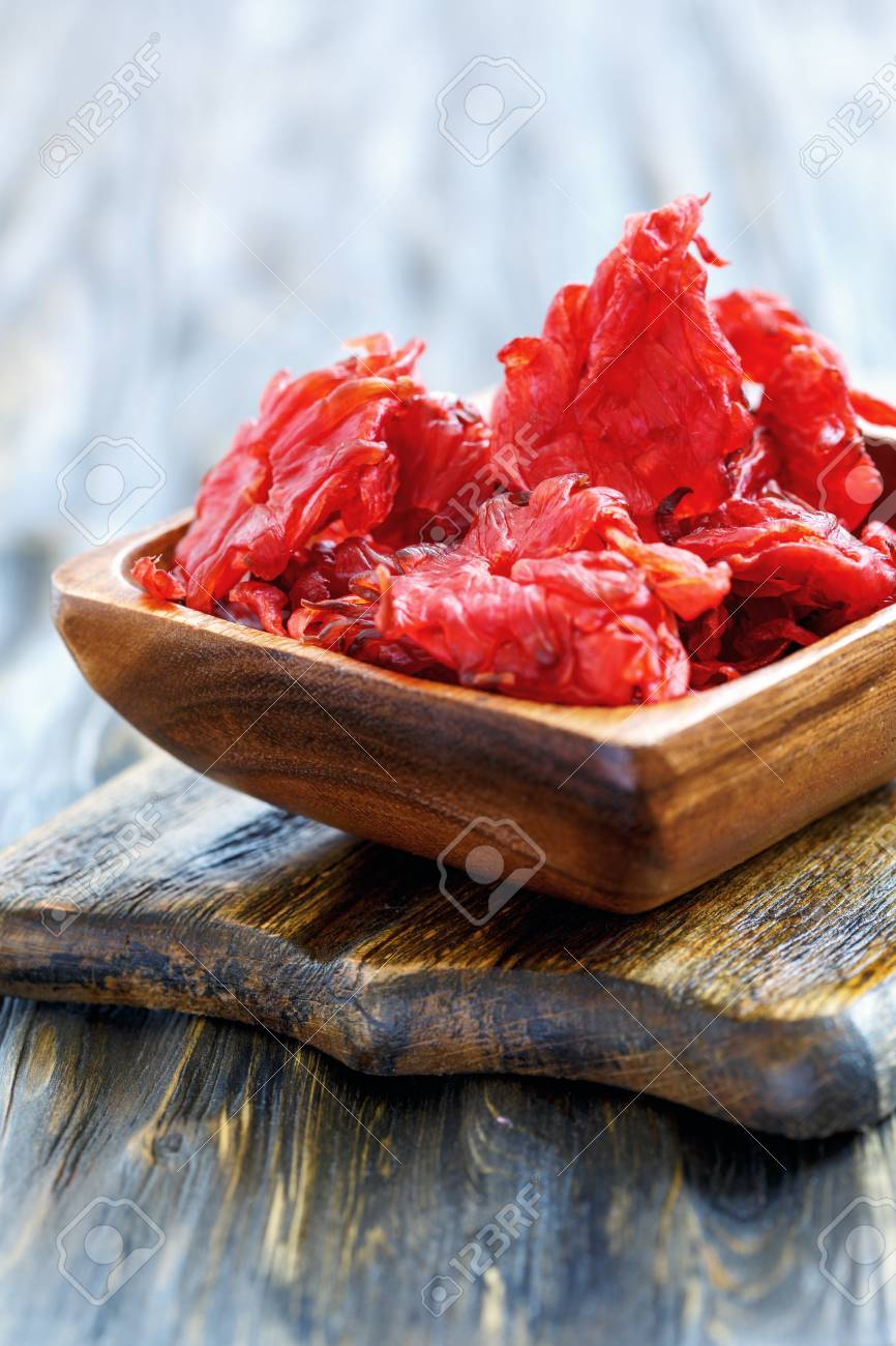 Candied Hibiscus Flowers In The Bowl On Wooden Table Selective