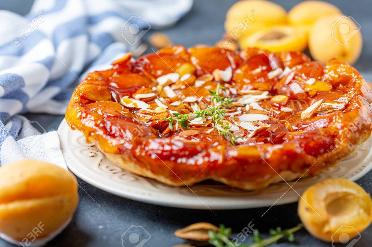 Homemade tarte tatin pie with apricots and almonds on a textured gray table, selective focus. - 128204542