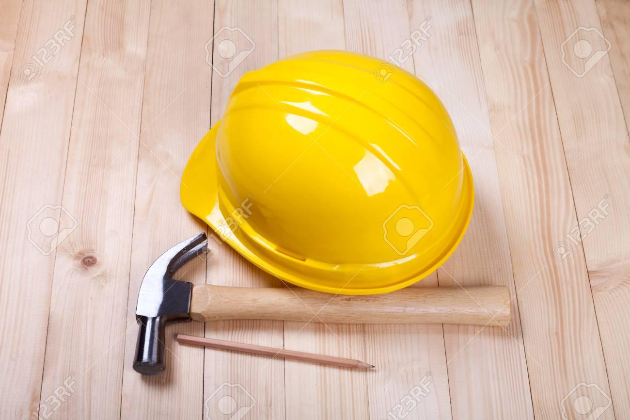 f5f808f99 Martillo, lápiz y con un casco amarillo en el fondo de madera