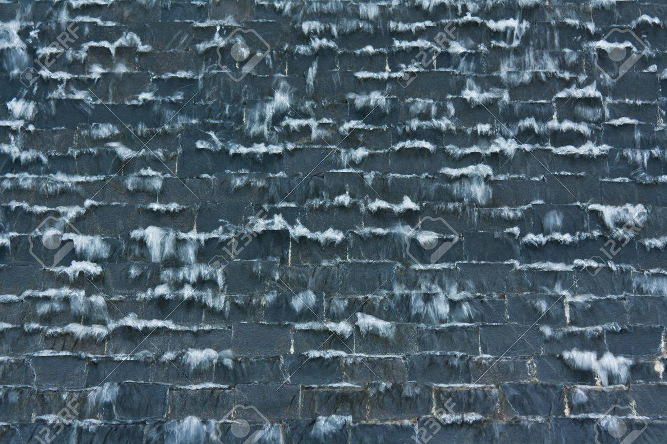 a waterfall on the black stone wall stock photo