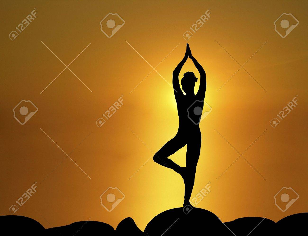 silhouette of woman in standing yoga pose with sunrise in the background Stock Photo - 2403101