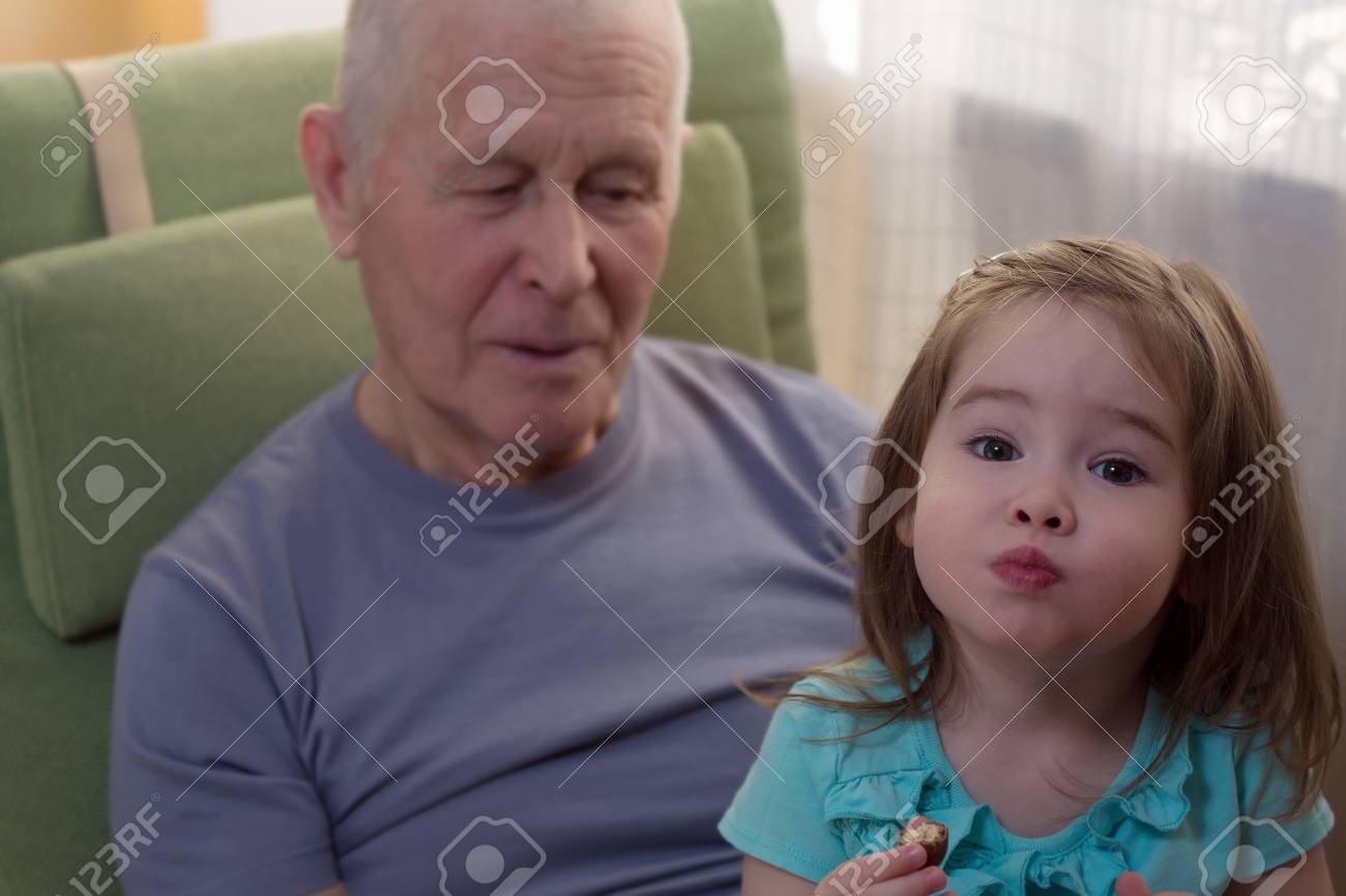 Cute little girl sitting with her grandfather - 34831925