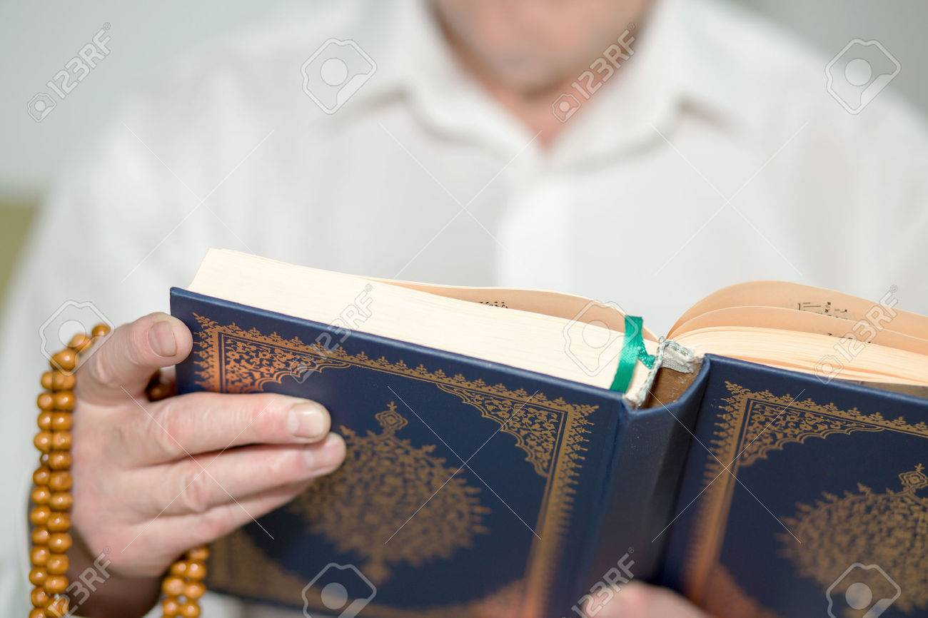 An old man's hand with rosary beads holding the Koran. Selective focus - 46041806