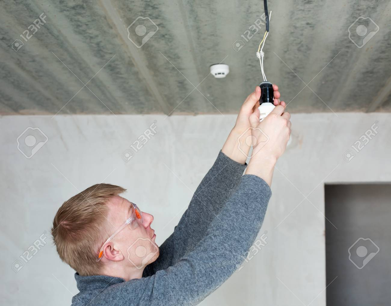 A man in safety glasses changing energy saving light bulbs - 47070189