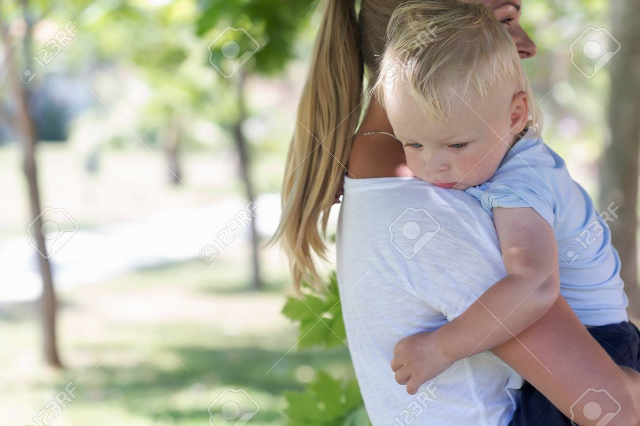 Outdoor portrait of mother and sad crying son in a summer park - 48600309