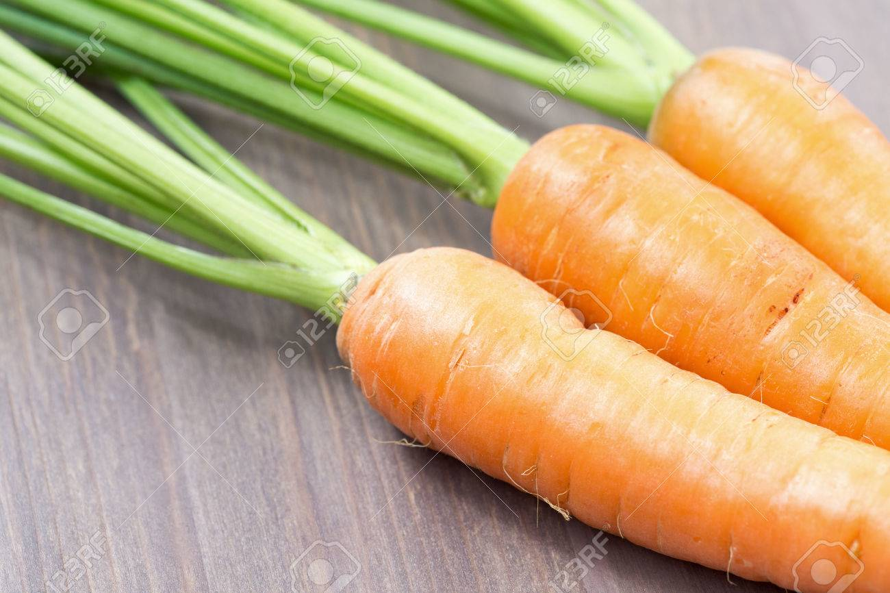 Raw carrots with green tops on wooden background - 50552346