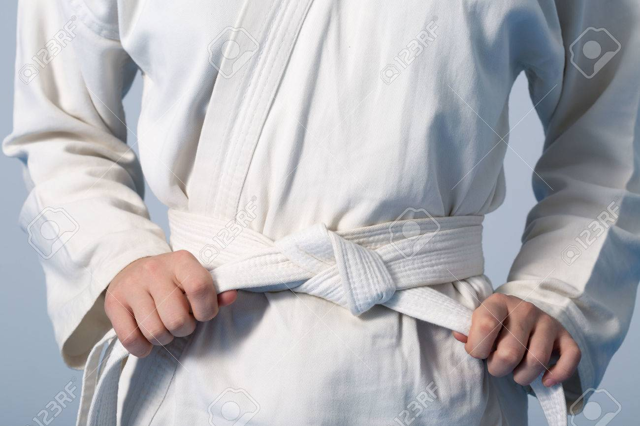 Hands tightening white belt on a teenage dressed in kimono for martial arts - 55408085