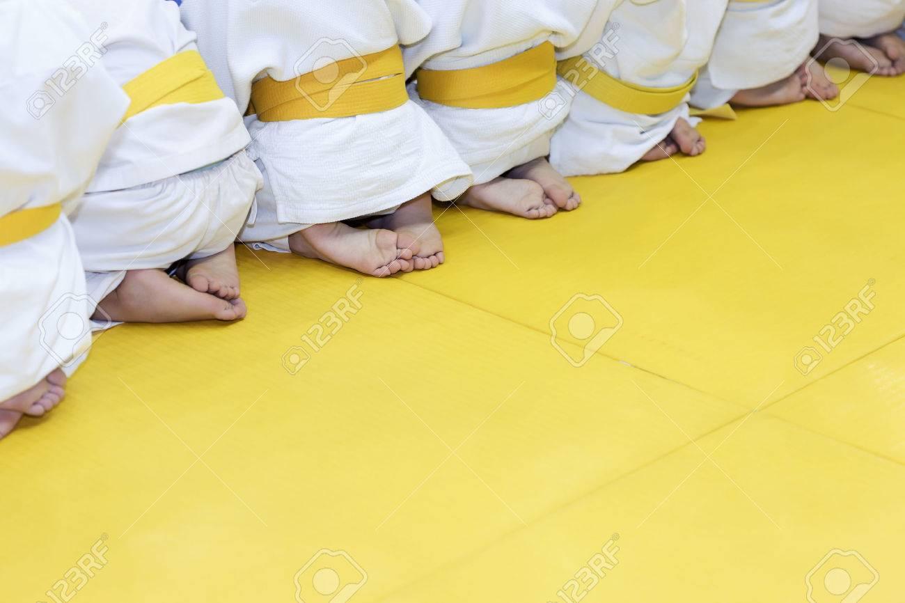 Group of children in kimono sitting on tatami on martial arts training seminar. Selective focus - 59881192