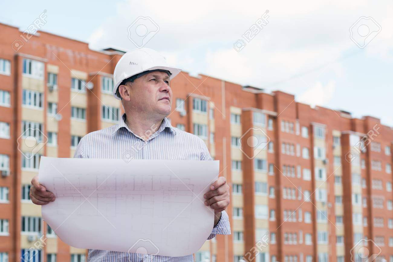 An Engineer With Construction Plans On A Background With An ...