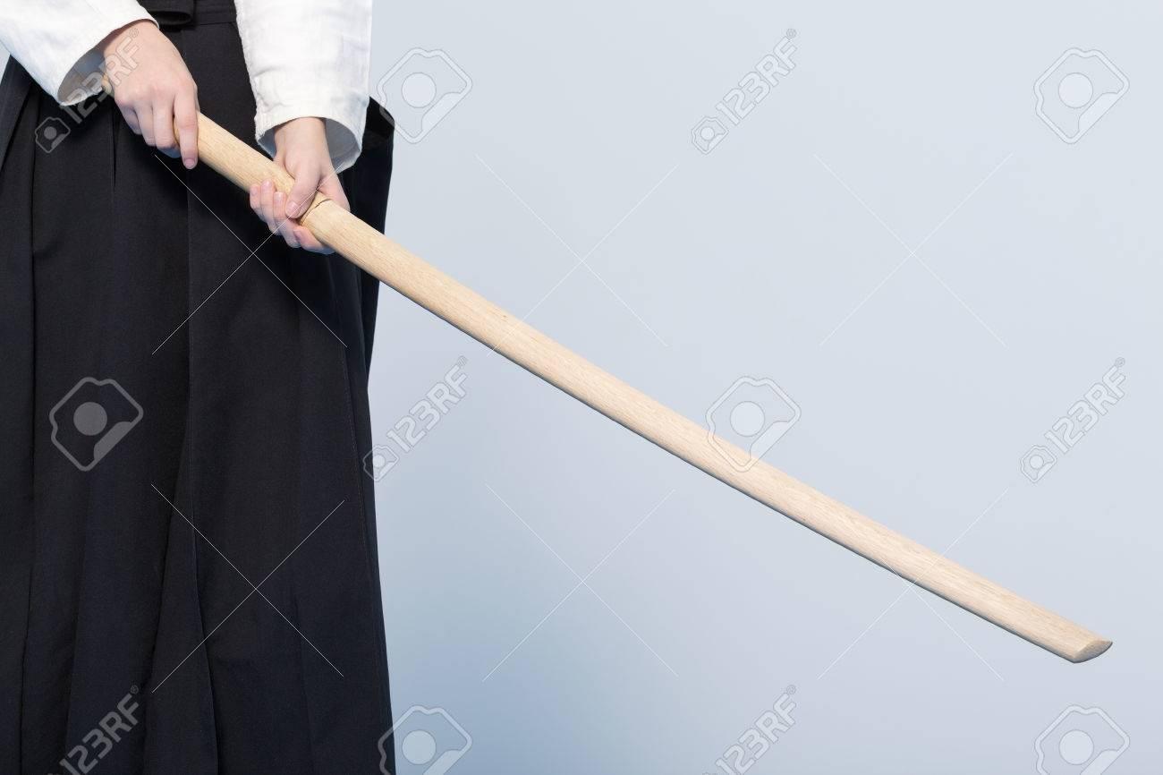 A girl in black hakama standing in fighting pose with wooden sword bokken - 61596834