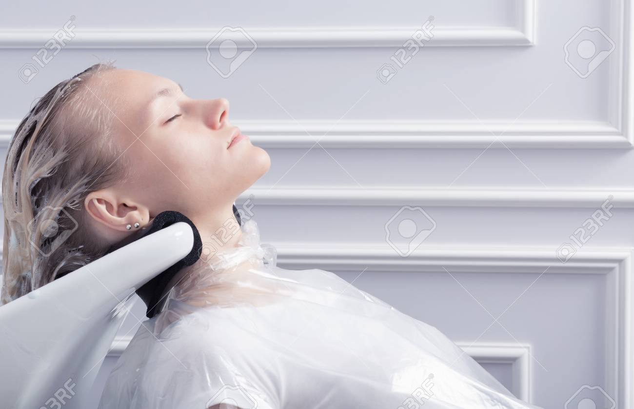 A blonde woman washing hair in hairdressing salon after hair coloring - 66820327